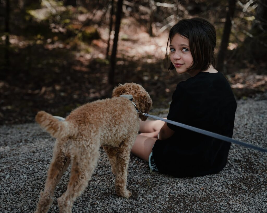 kid sitting on ground with poodle near forest